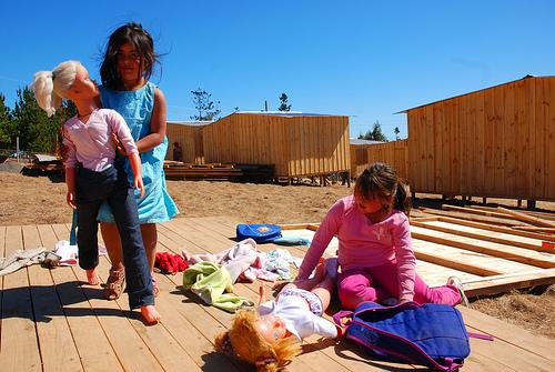 """Dziewczynki bawią się w """"mediagua"""" (tymczasowej osadzie) w obozie dla wysiedleńców w miejscowości Lipimávida w Vichuquén, niedaleko Maule. Zdjęcie autorstwa Rodrigo Alvareza, wykorzystane na podstawie licencji Creative Commons."""
